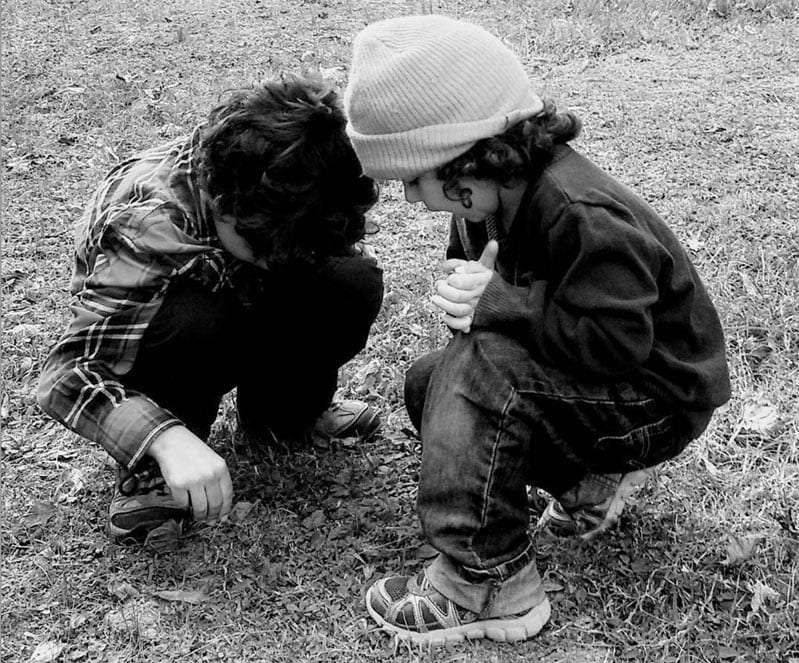 two young children examine something in the grass beneath their feet