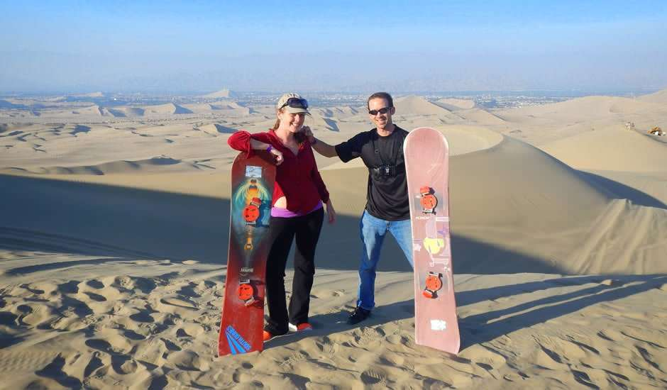 a couple standing at the top of a sand dune, holding sandboards