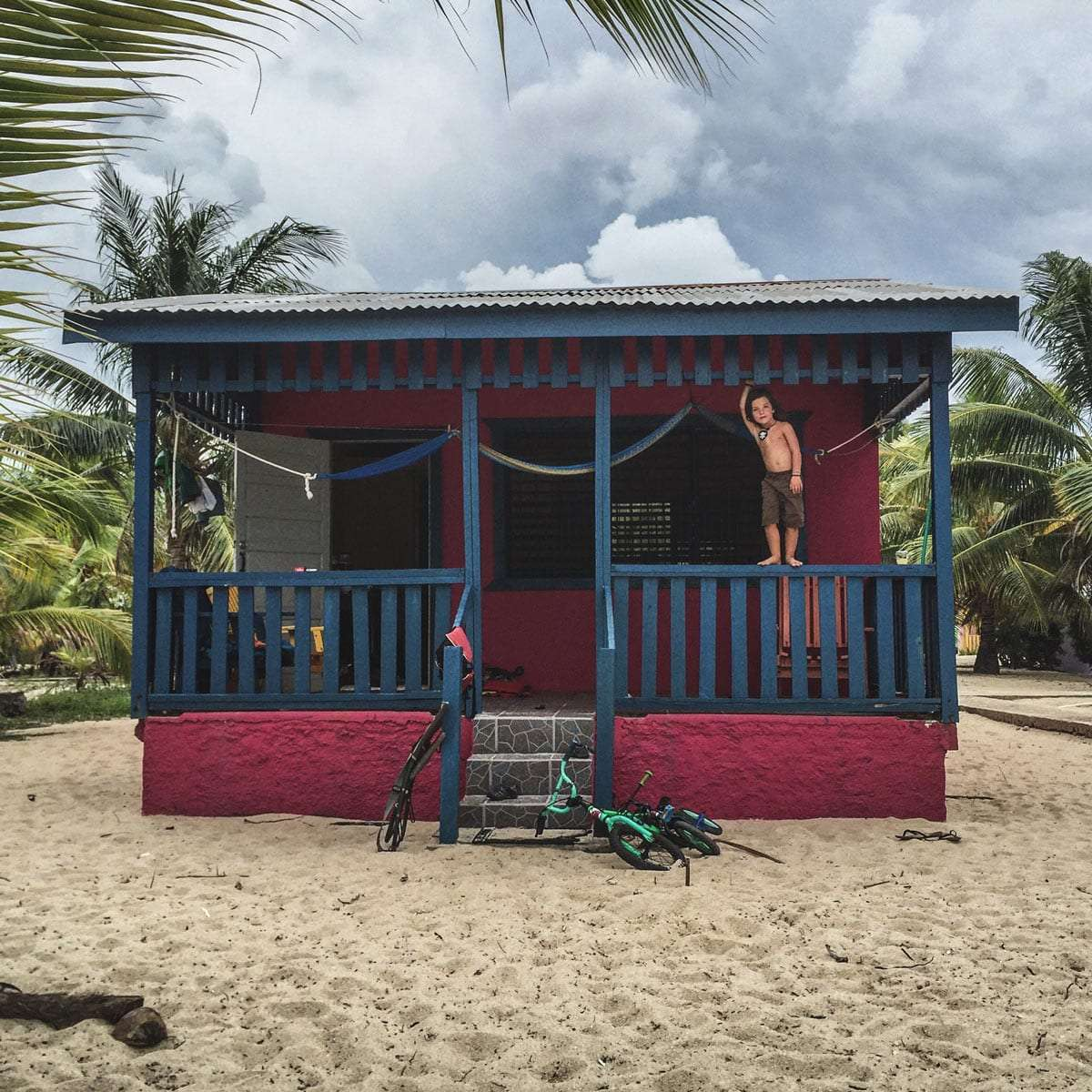 a young boy stands on the railing of a cabana in placencia, belize