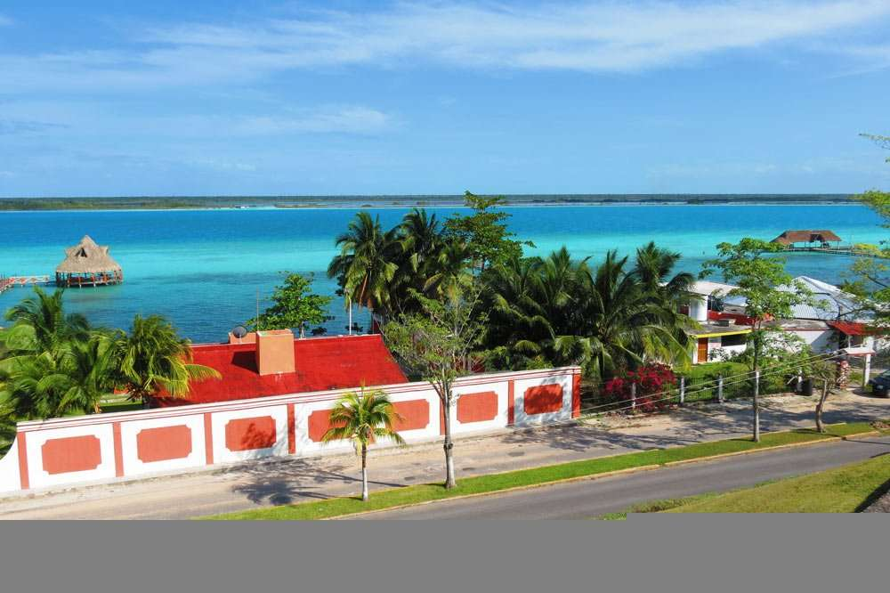 a vibrant red and white fence and building, surrounded by palm trees, the blue waters of the Laguna Bacalar in the distance