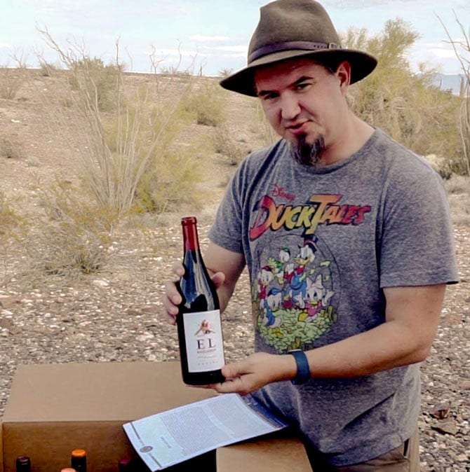 a man wearing a ducktales t-shirt and spiffy hat holding a bottle of wine he produced from a box