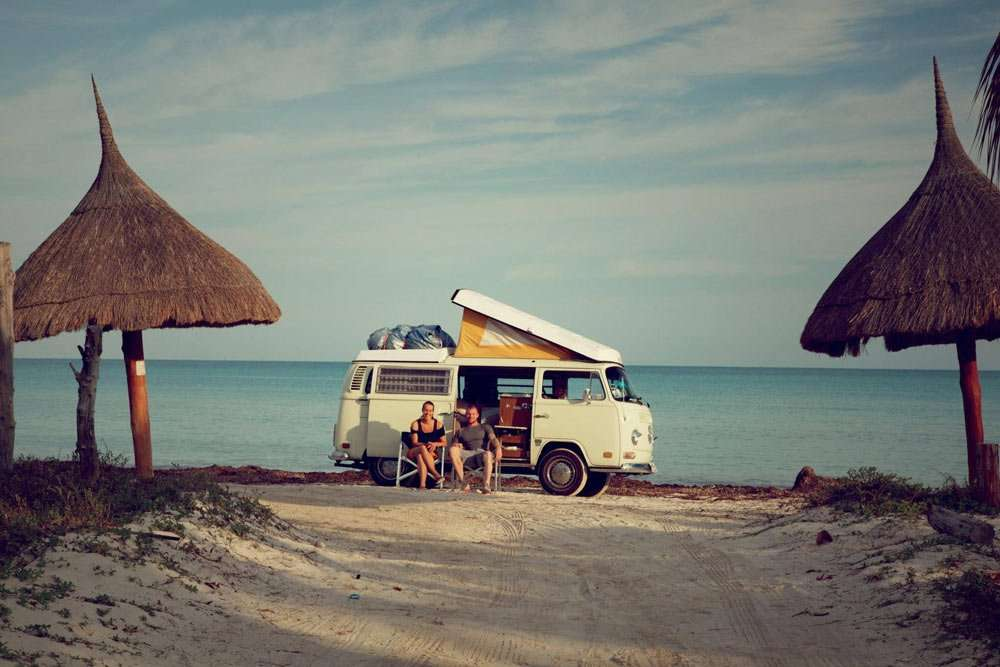 a VW Bus campervan parked near the beach
