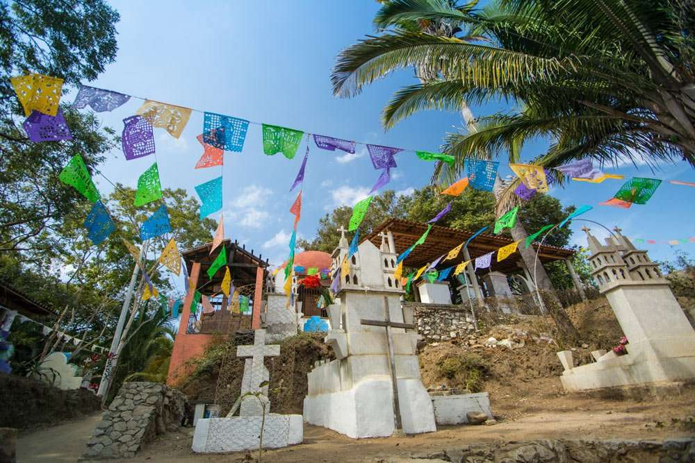 prayer flags hung around a cemetery on a hill