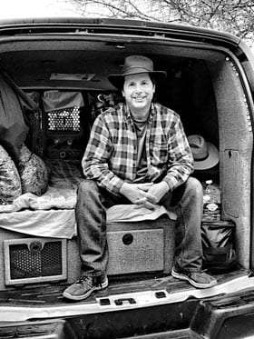 a man sitting in the rear doorway of a cargo van, customized for his travels