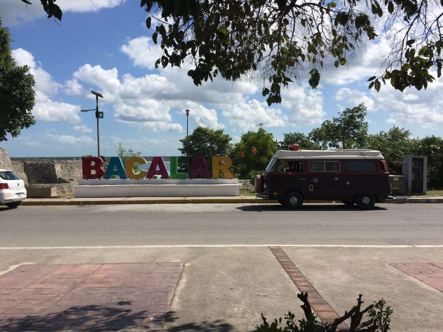 a VW Bus parked near a sign that colorfully reads Bacalar