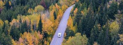 an rv driving through an autumn forest on a lonely road