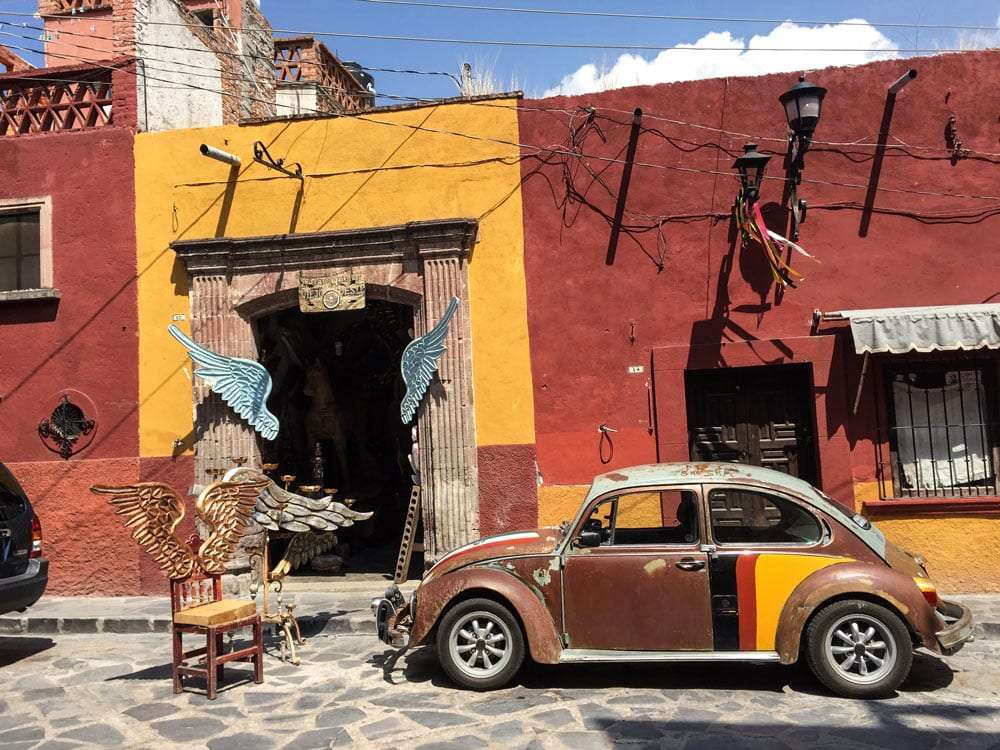 a volkswagen beetle parked in the street, painted to match the orange and red walls it would seem.