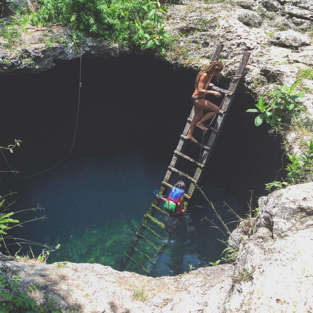a mom and her son climb a ladder out of a cenote