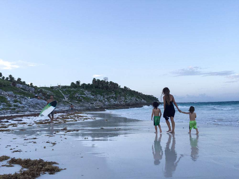 a family walks a beach toward some ruins