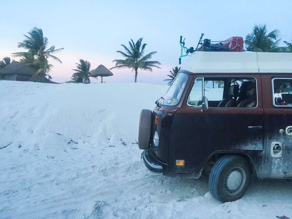 a VW Bus parked in some pristine sand