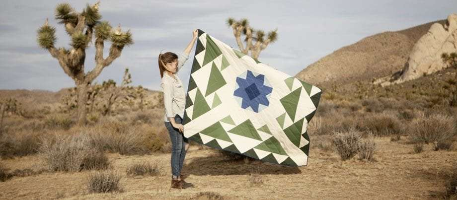 a woman holding up a gorgeous quilt in Joshua Tree National Park
