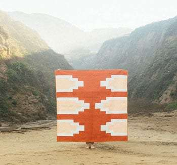 a beautiful orange and peach quilt held up against a valley background