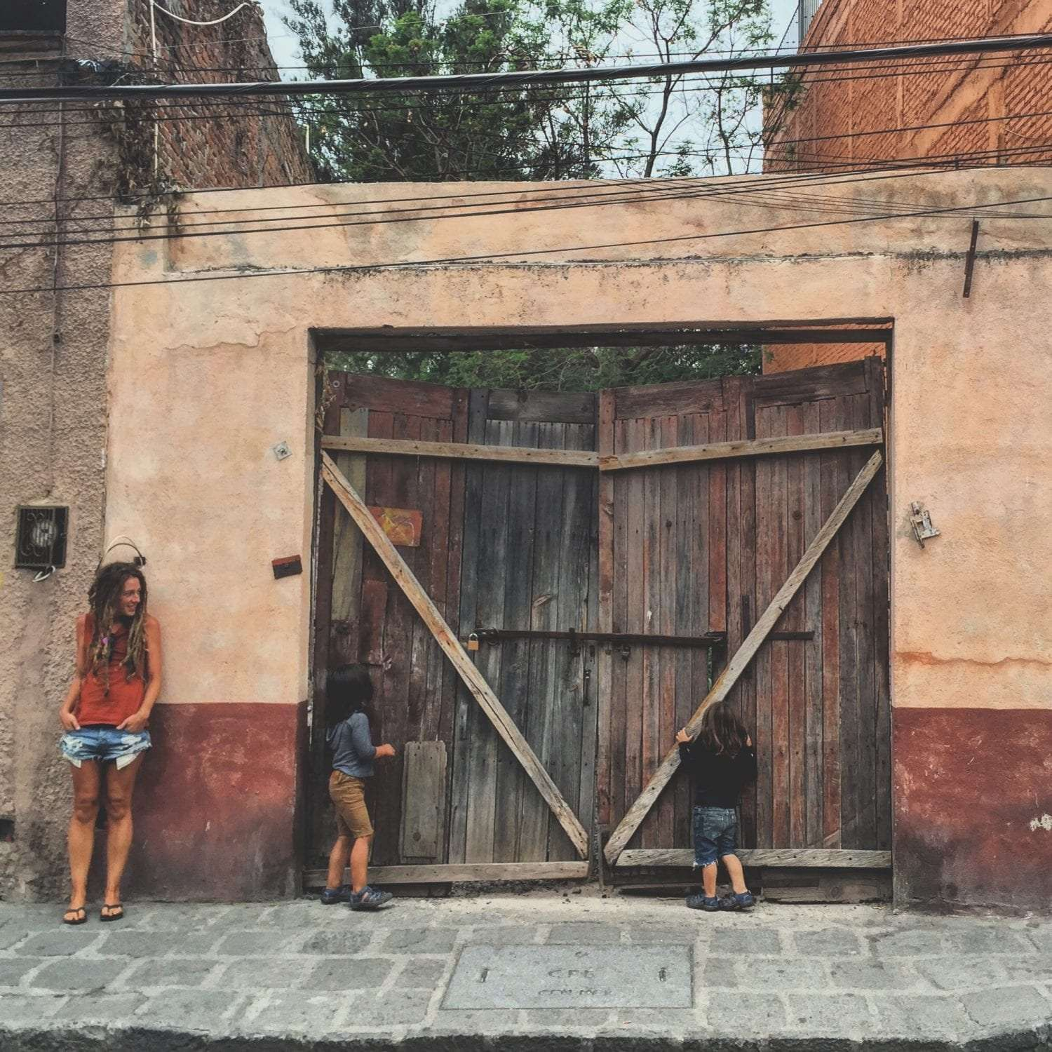children stand beside an old wooden gate