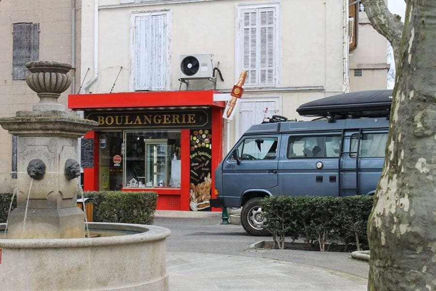 a vanagon parked near a boulangerie, aka bakery