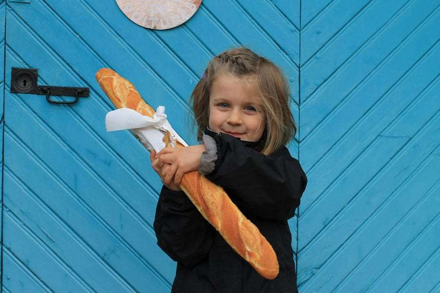 a girl holding a large loaf of bread