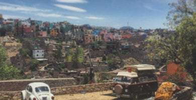 a vw bus and a vw beetle parked above guanajuato