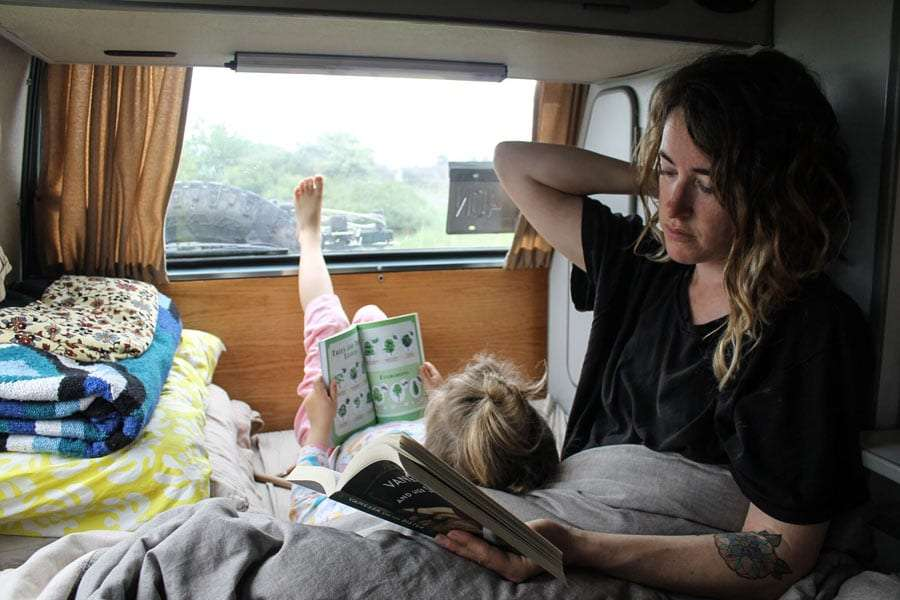 a mother and daughter reading books in the back of their Vanagon