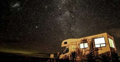 an rv parked beneath a starry sky in a national park