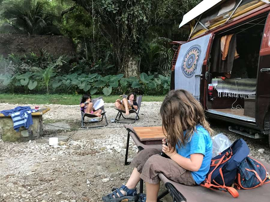 three young children draw pictures, sitting outside of a VW Bus near Palenque National Park