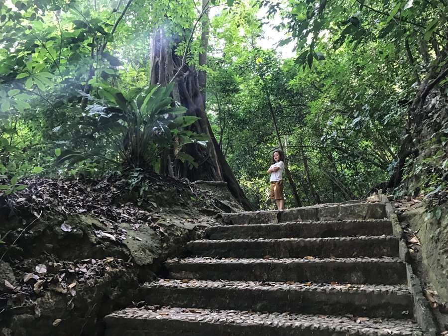 a boy standing atop stone stairs in Palenque National Park