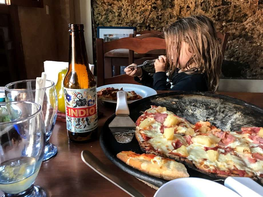A boy playing with a wine opener at a pizza place
