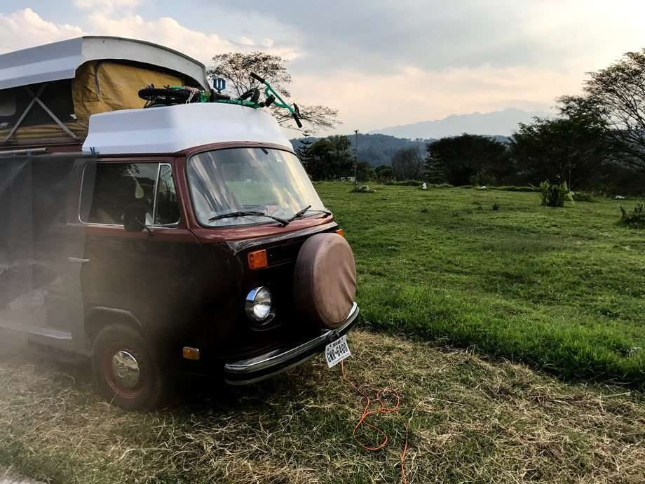 a Volkswagen Bus parked in a field, mountains in the background