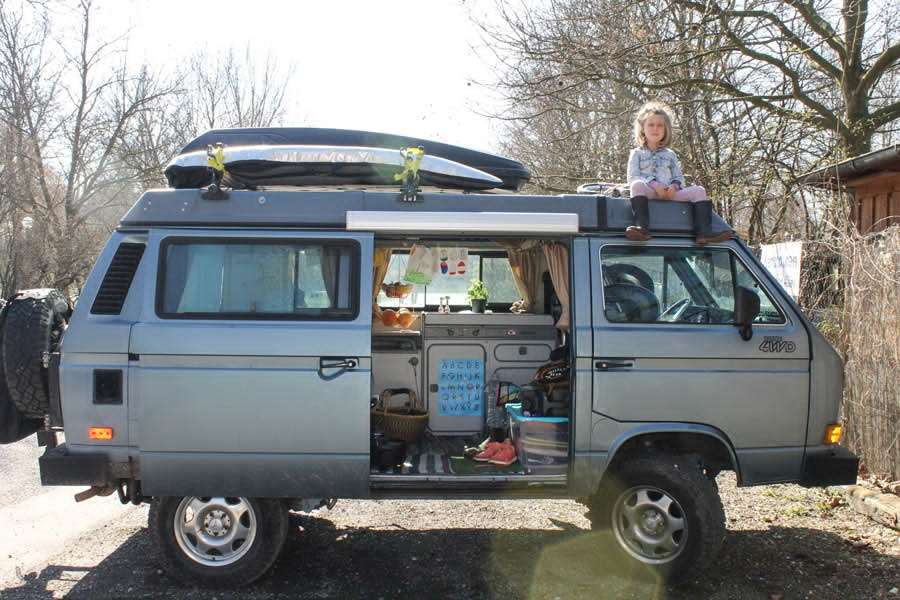 a gun metal blue vanagon with a young girl sitting on the roof, door open