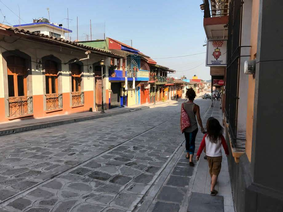 a family walks the sidewalk of a street in a Mexican pueblo