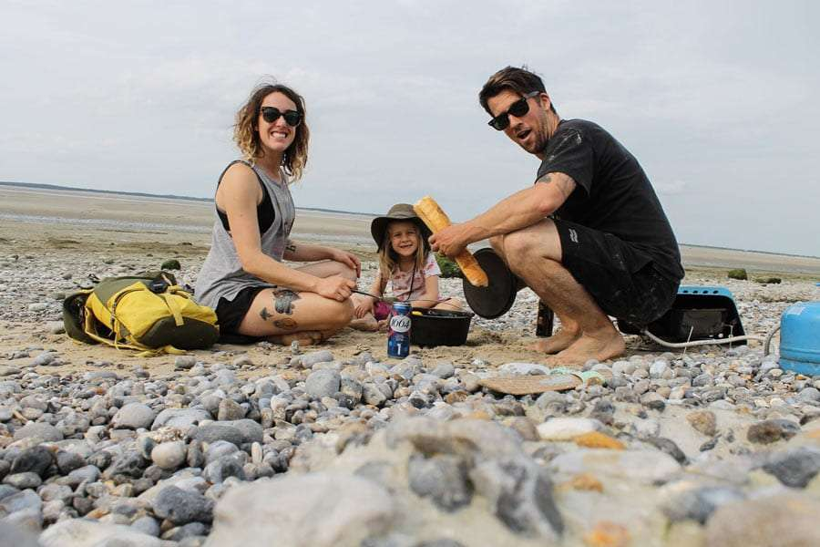 a family eating a picnic on the beach