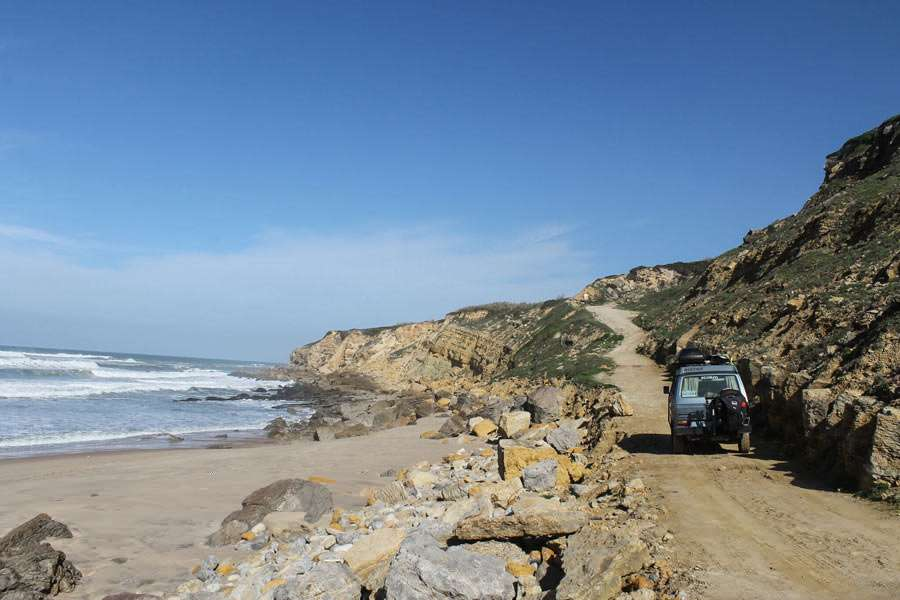 a vanagon driving down a dirt road along the coast