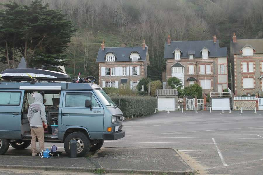 a man stands outside of his 1987 Syncro Vanagon in Europe