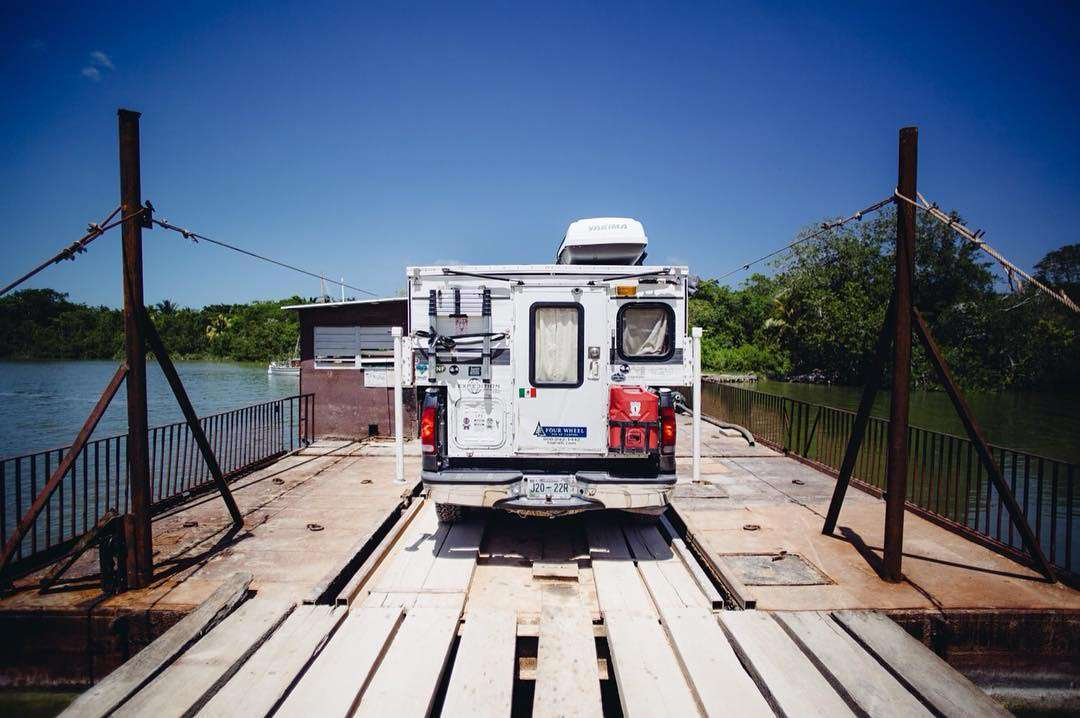 a four wheel camper on the back of a ford f-250, on a rickety wooden ferry near Corozal, Belize