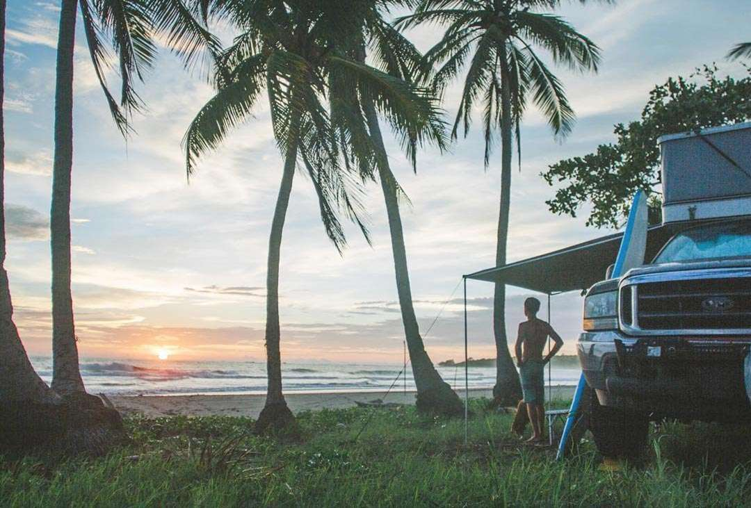 Pete looks over the ocean, the sun setting against their truck camper between the palm trees