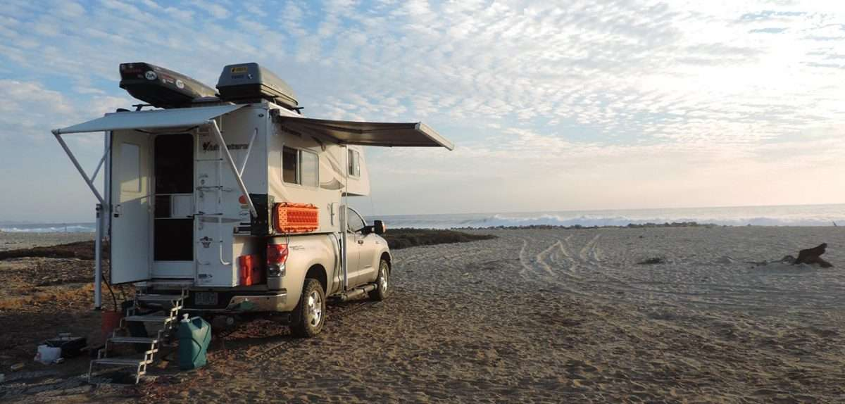 a beautiful truck camper, decked out for travel, on a beach