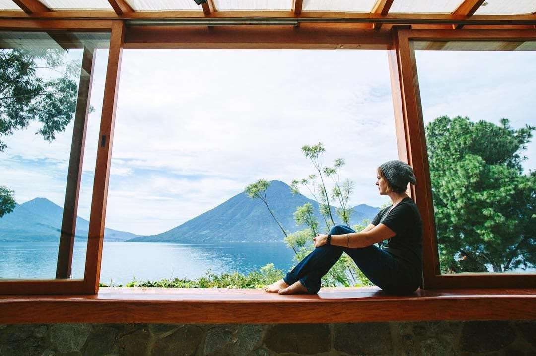 a woman sits in a wooden window, open to the mountains and lake beyond