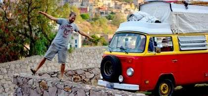a young man walks a stone wall in Guanajuato, Mexico, his red and yellow VW Bus parked nearby