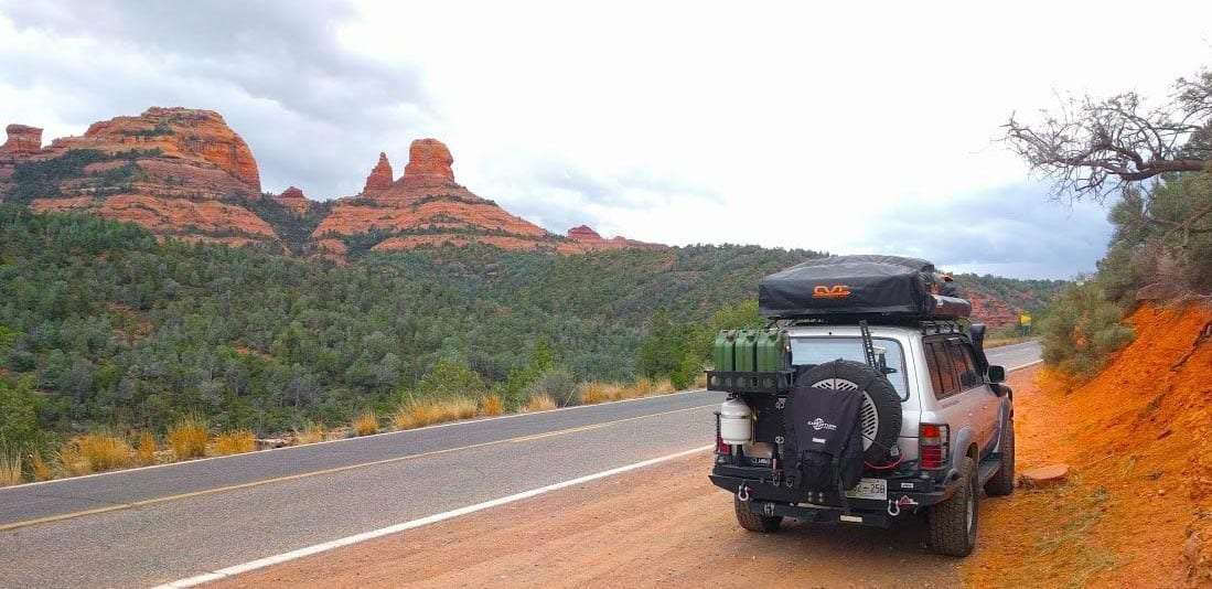 a toyota landcruiser parked alongside a road with gorgeous red rock spires in the distance