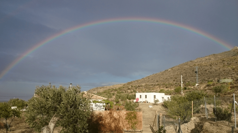 a rainbow over a small village