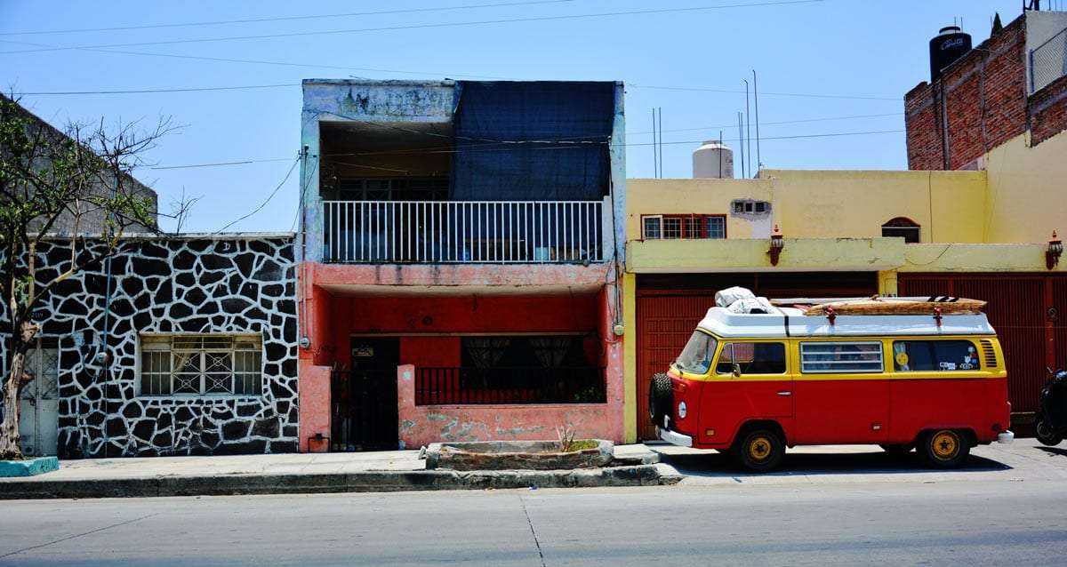 a bay window volkswagen Bus parked on a street in Mexico