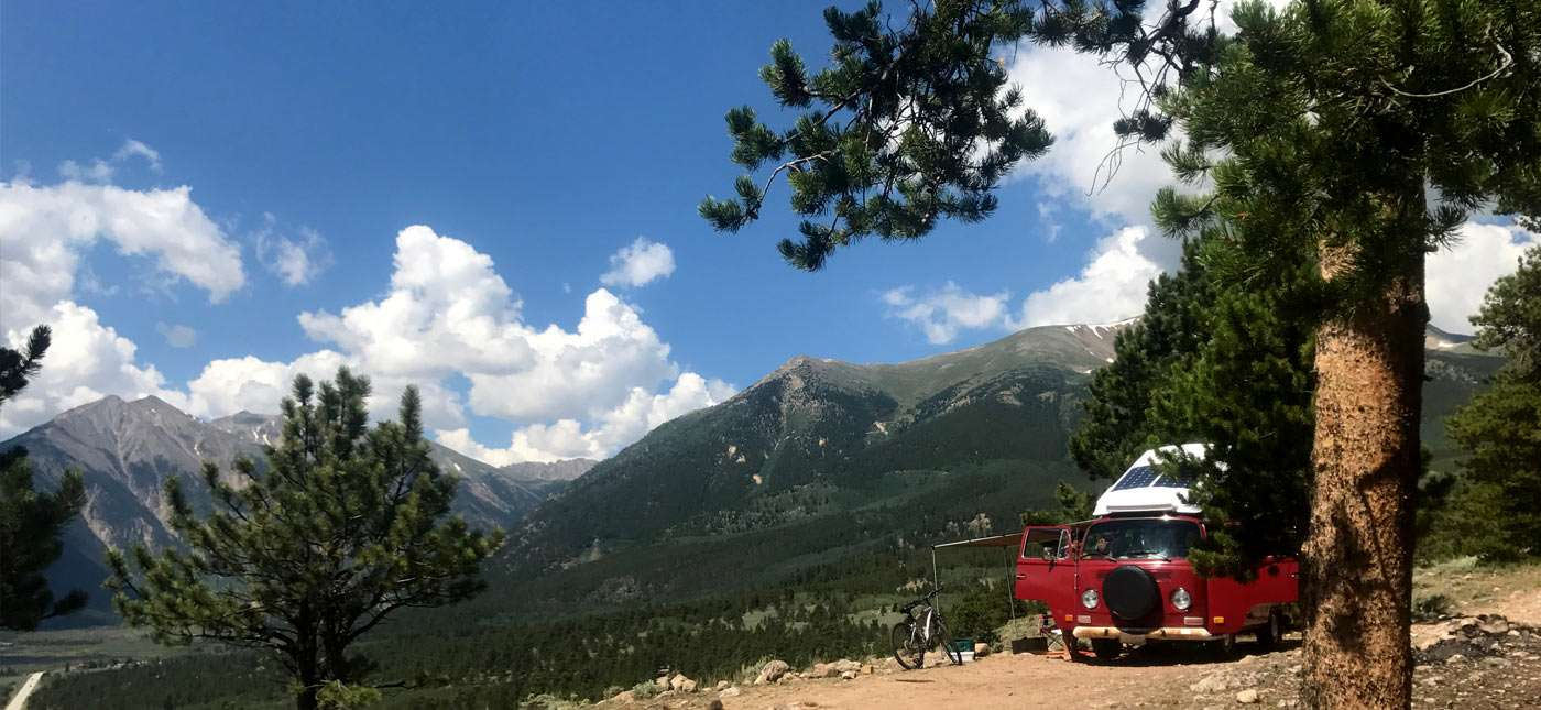 a red 1972 Volkswagen Bus parked atop a mountain
