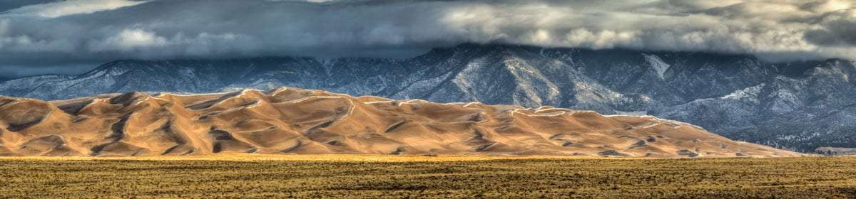 a prairie, sand dunes and towering snowy mountains