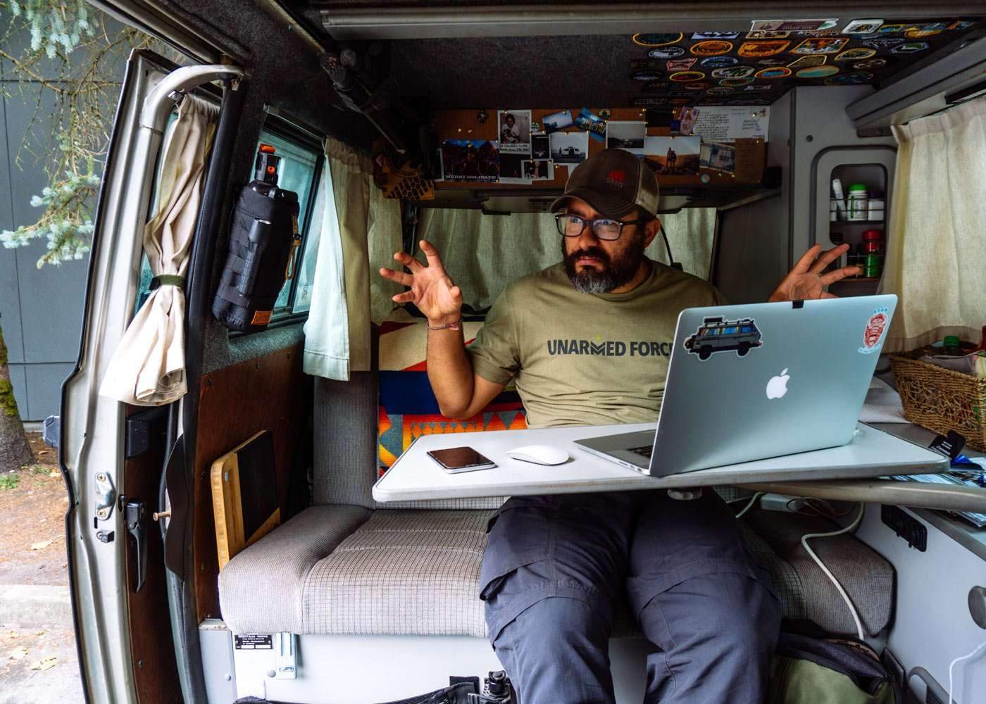 a bearded young man working on a macbook from a VW vanagon