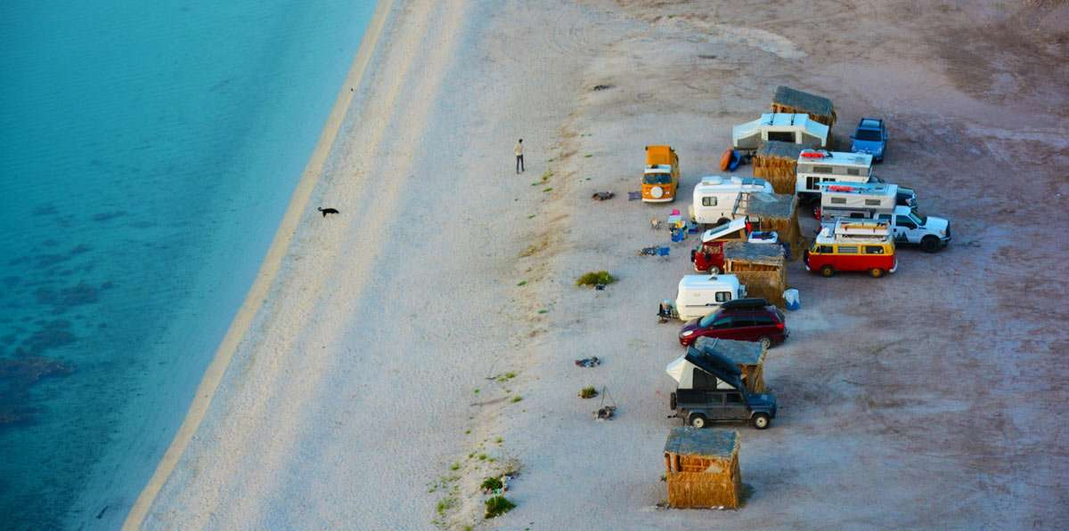 a host of various campers on a beach in Baja California