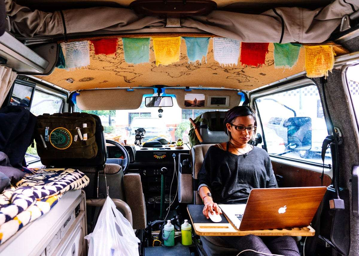 a young woman working from her van