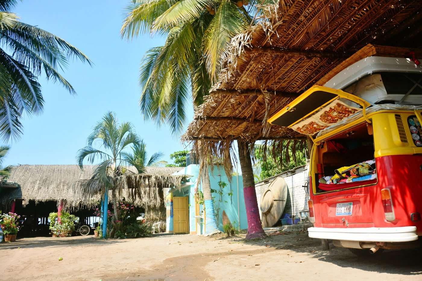 a red and yellow vw bus parked in a carport in Mexico