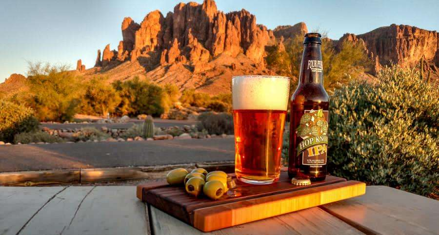 an ipa and olives on a wooden cutting board in front of a mountain scene