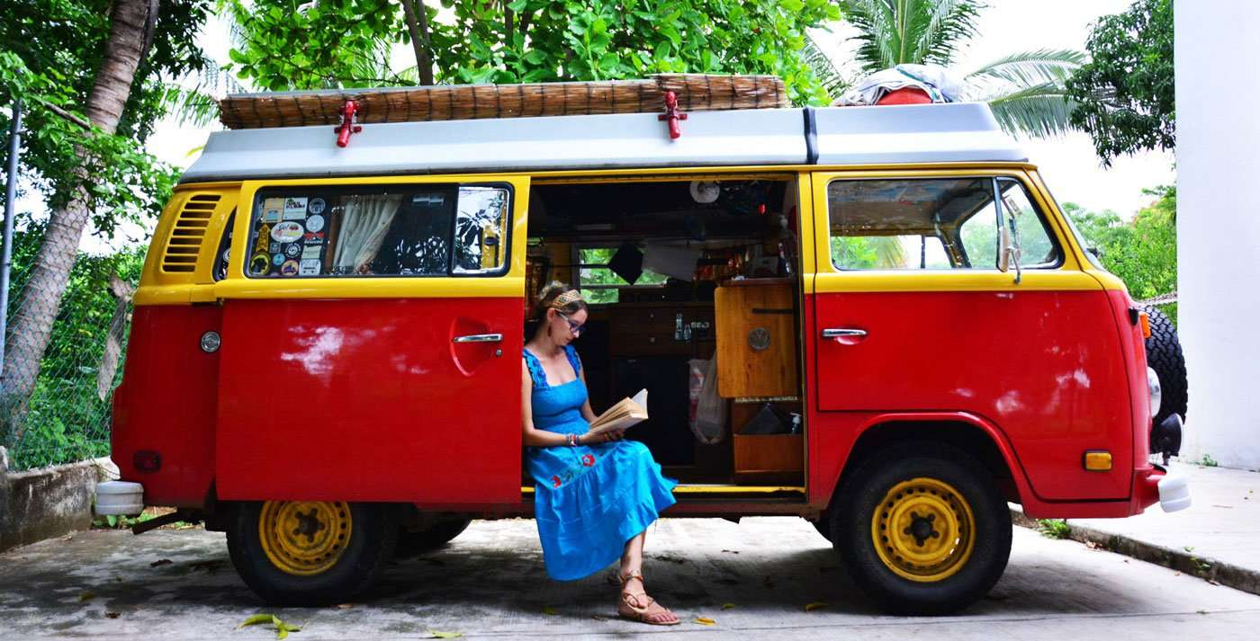 emma sitting in the doorway of a baywindow volkswagen bus, studying a spanish book