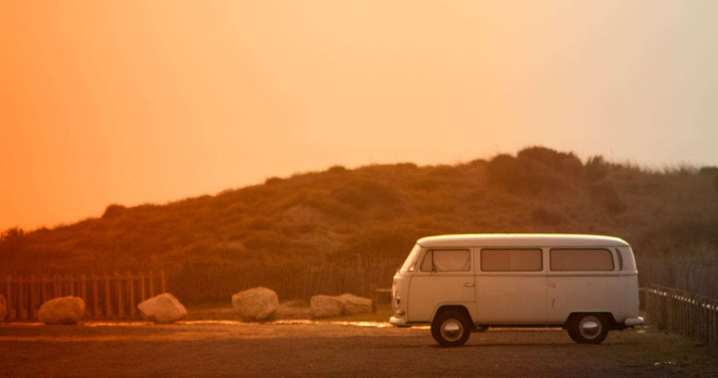 a tin top volkswagen bus in a parking lot surrounded by desert