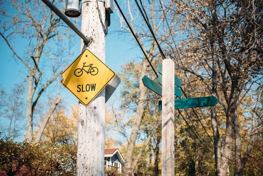 a sign reads slow and shows a bicycle on a road