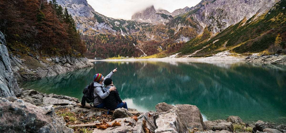 a couple sitting near an alpine lake enjoying their travels